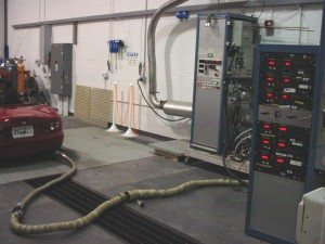Photo: Hose connected to vehicle tailpipe; sending emissions to test equipment