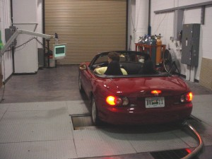 Photo: Driver running car through test cycle on dynamometer